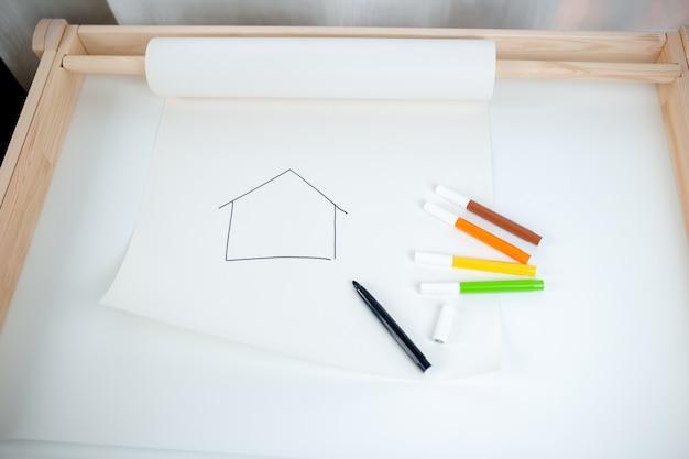 Rysować na papierowej rolce na bielu stole. rysunek domu z kolorowymi markerami, pozostań w domu, zachowaj bezpieczeństwo podczas kwarantanny.