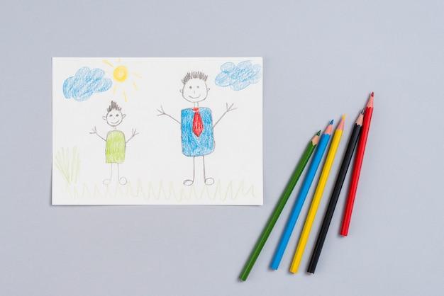 Rysować ojciec i syn na papierze z ołówkami
