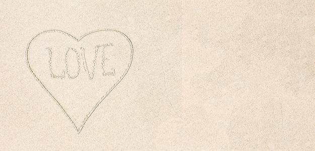 Rysowane serce z miłością słowa na białym piasku, z bliska, widok z góry. białe tło piasku, miejsce na kopię