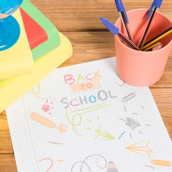 Rysowanie kolorami na papierze z powrotem do szkoły na drewnianym stole z książkami i ołówkami