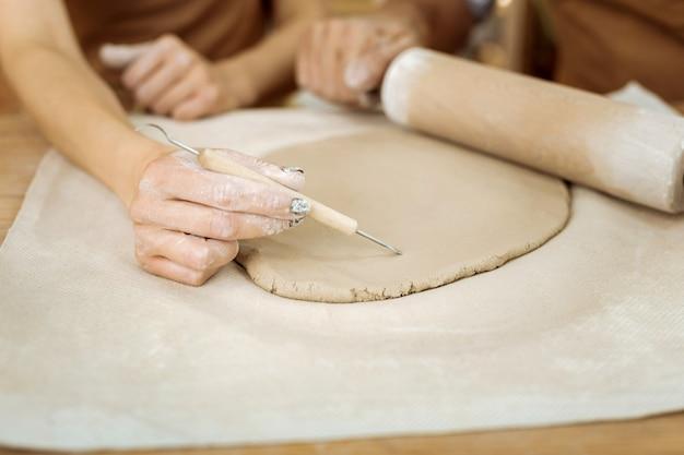 Rysowanie linii. słynna zręczna ceramistka podczas ciężkiej pracy rysująca linie na przyszłym wazonie ceramicznym