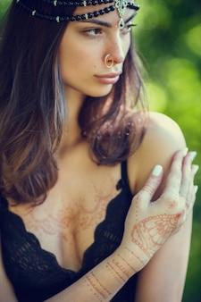 Rysowanie mehndi za pomocą henny na rękach i plecach dziewczyny