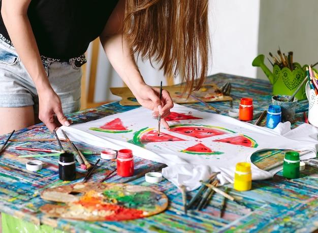 Rysowanie na ubraniach. dziewczyna rysuje na białej koszulce.