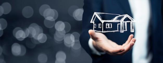 Rysunek domu w ręce człowieka na ekranie