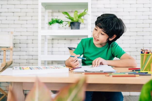 Rysunek dziecka kolorowymi kredkami na białym papierze z uśmiechem na drewnianym stole. twórczość dzieci wyrażona poprzez sztukę w przedszkolu i szkole podstawowej. powrót do szkoły.