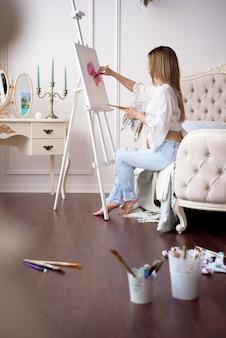 Rysunek malarza w pracowni plastycznej przy użyciu sztalugi portret młodej kobiety malowanie farbami olejnymi na białym płótnie, portret widok z boku