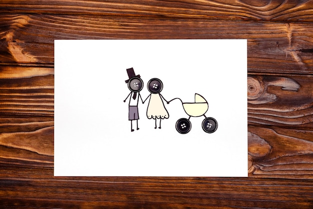 Rysunek młodych rodziców z wózkiem na drewnianym stole. pojęcie rodziny. widok z góry
