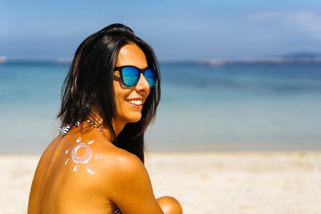 Rysunek ochrony przeciwsłonecznej na ramieniu opalonej, uśmiechniętej kobiety na plaży