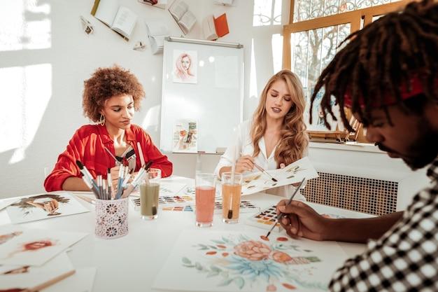 Rysunek przyjaciela. ciemnowłosa kręcona kobieta dołącza do swoich blondwłosych przyjaciół, rysujących na lekkim studio