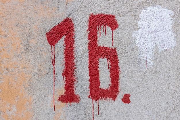 Rysunek szesnaście czerwoną farbą z sedtami na kamiennej ścianie domu. siniak. zdjęcie wysokiej jakości