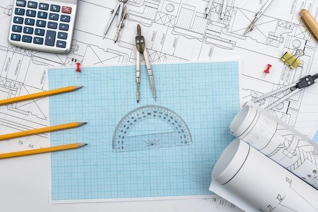 Rysunek techniczny, papier milimetrowy i narzędzia. zespół biurowy inżyniera pracujący z planami.