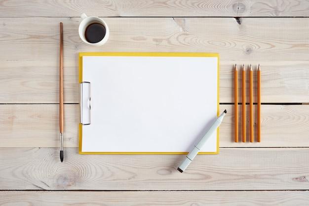 Rysunek ustawiony na białym drewnianym stole. kilka ołówków, pędzel, marker i tablet z białym papierem na stole. flatlay.