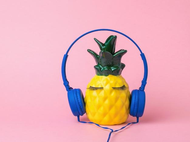 Rysunek żółtego ananasa w niebieskich słuchawkach na czerwonym tle. pojęcie globalnej digitalizacji.