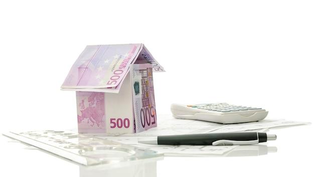 Rysunki architektoniczne i narzędzia z domem pieniędzy.