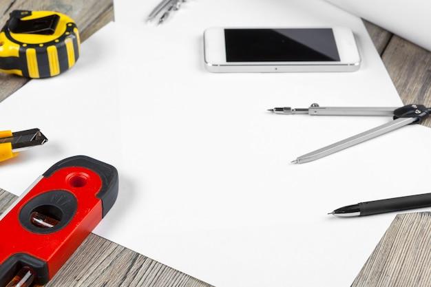 Rysunki architektoniczne. instrumenty na stole roboczym. pusty arkusz papieru