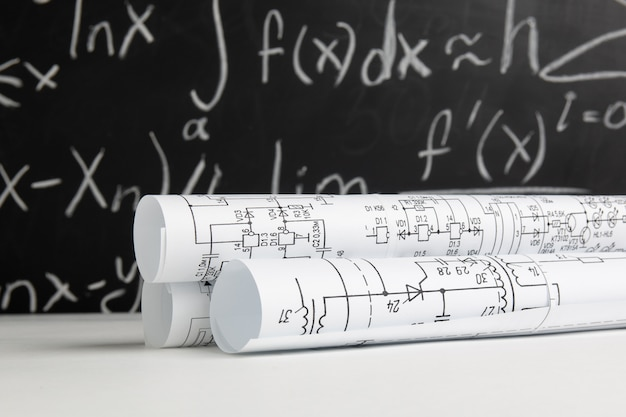 Rysunki elektrotechniczne na białym stole na tle tablicy z formułami matematycznymi