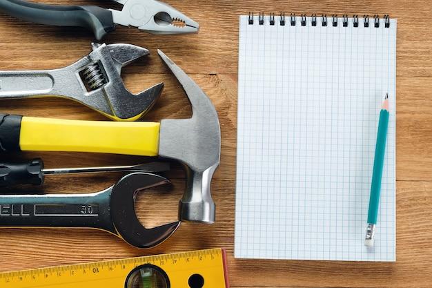 Rysunki i narzędzia do profesjonalnej budowy lub naprawy domu, na drewnianym stole.