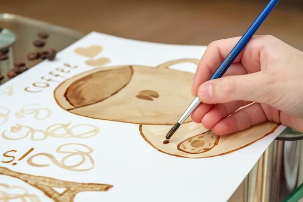 Rysunki kawy. dziewczyna rysuje filiżankę kawy przy użyciu kawy zamiast farb