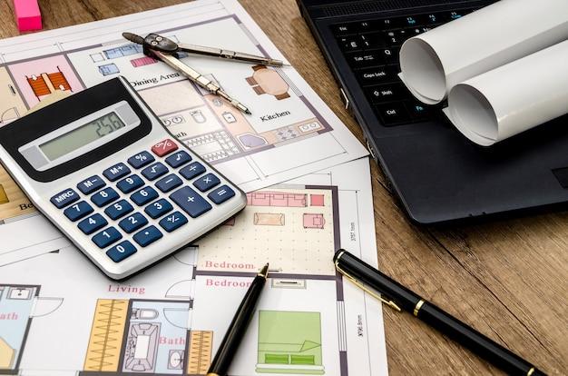 Rysunki na papierze z laptopem i kalkulatorem