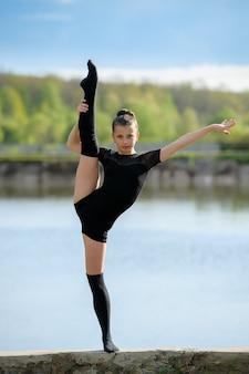 Rytmiczna gimnastyczka robi pionowej nodze rozszczepiającej