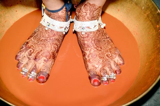 Rytuał griha pravesh – prawe stopy nowo poślubionej hinduskiej panny młodej w sari, która wchodzi na talerz wypełniony płynnym kumkumem przed pierwszym wejściem do domu