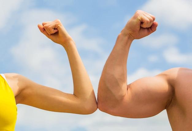 Rywalizacja, vs, wyzwanie, porównanie siły. sportowy mężczyzna i kobieta. muskularne ramię a słaba ręka. vs, walcz ciężko. konkurencja, porównanie sił. koncepcja rywalizacji. ręka, ramię mężczyzny, pięść. zbliżenie