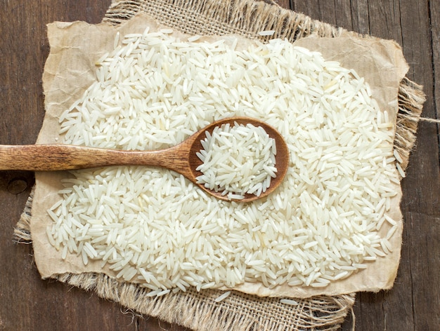Ryż basmati z łyżką na brązowym drewnianym stole