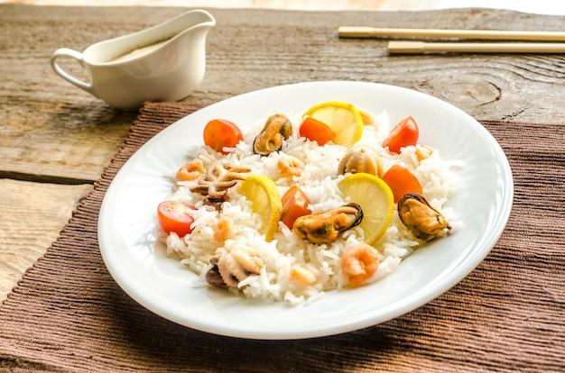 Ryż basmati z owocami morza na drewnianym stole