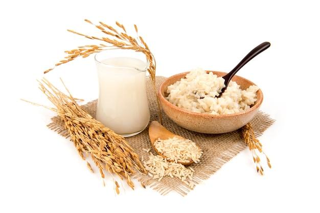 Ryż brązowy, ryż gotowany na parze i woda z brązowego ryżu na białym tle.