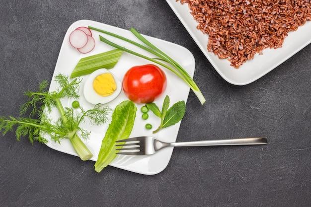Ryż brązowy w białym talerzu połowa pomidora i ziół w białej misce