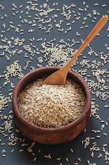 Ryż brązowy w drewnianej misce z drewnianą lub bambusową łyżeczką