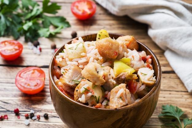 Ryż duszony z kurczakiem i warzywami w drewnianej misce.