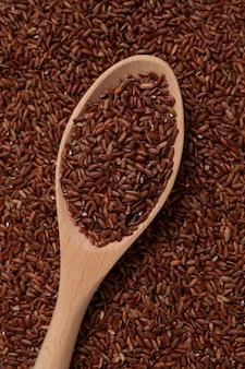 Ryż gaba w drewnianej łyżce leżącej na ziarnach. kiełkuj brązowy ryż.