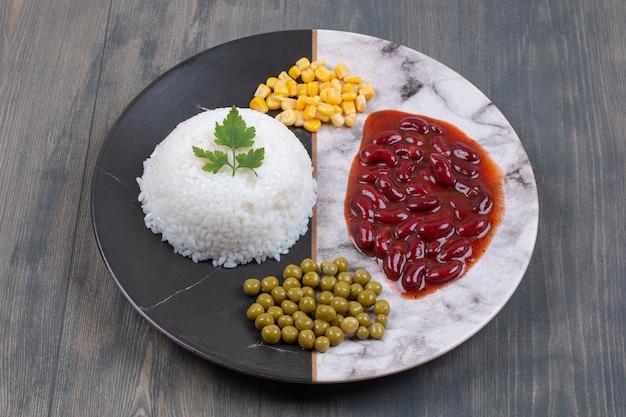 Ryż gotowany na parze, kukurydza w puszkach i groszek na talerzu