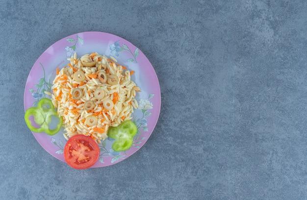 Ryż gotowany na parze z posiekanymi warzywami na fioletowym talerzu.