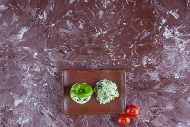 Ryż i papryka na talerzu obok pomidorów na marmurowej powierzchni