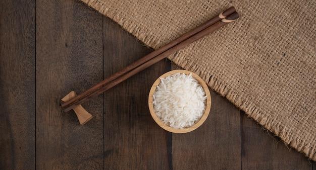 Ryż jaśminowy w drewnianej misce i pałeczkę na worze, tło stołu jutowego z miejsca kopiowania, widok z góry