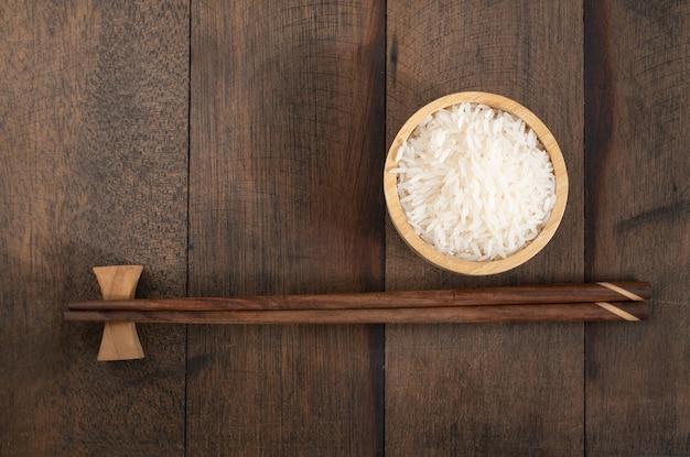 Ryż jaśminowy w drewnianej misce i pałeczki na tle nieczysty stół z drewna z miejsca na kopię, widok z góry