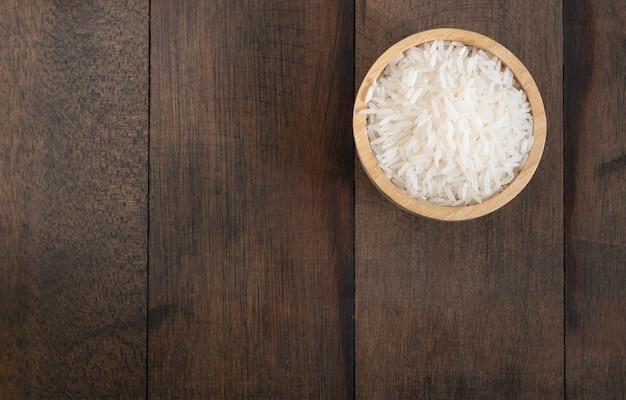 Ryż jaśminowy w drewnianej misce na tle nieczysty drewniany stół z miejsca na kopię, widok z góry