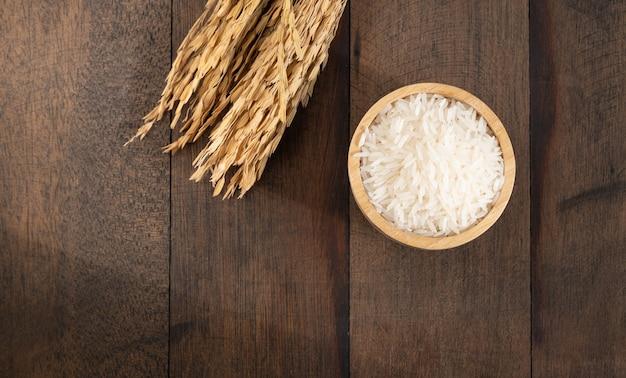 Ryż jaśminowy w drewnianej misce na tle nieczysty stół z drewna z miejsca na kopię, widok z góry