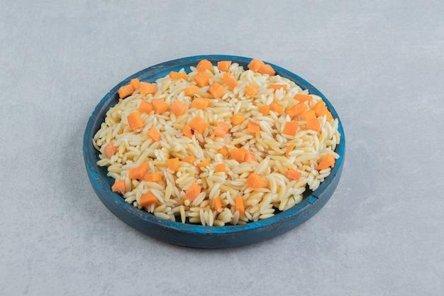 Ryż marchewkowy na drewnianym talerzu, na marmurze.