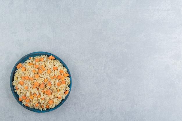 Ryż marchewkowy w drewnianym talerzu, na marmurowym tle.
