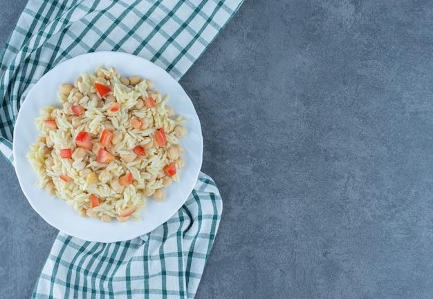 Ryż na parze z groszkiem i plastrami pomidora na białym talerzu.