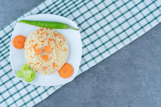 Ryż na parze z posiekaną marchewką na białym talerzu.