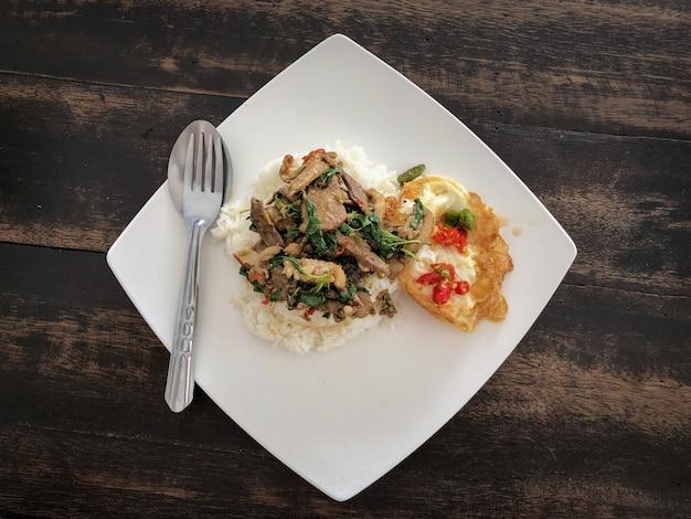 Ryż posypany smażoną kaczką i bazylią z jajkiem sadzonym