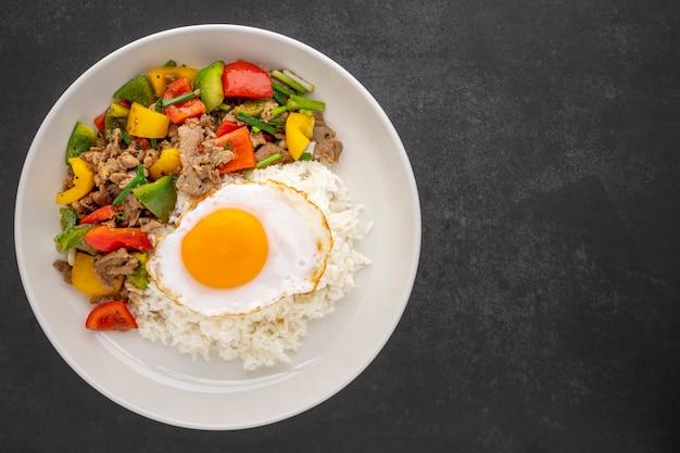 Ryż posypany smażoną wołowiną z czarnym pieprzem, czerwoną, żółtą, zieloną papryką słodką, papryką lub papryką, szczypiorkiem i jajkiem w talerzu ceramicznym na ciemnym tle tekstury, widok z góry