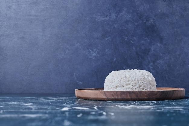 Ryż przyozdobiony na drewnianym talerzu.