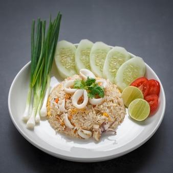 Ryż smażony z kalmarem podawany ze szczypiorkiem, ogórkiem, kolendrą, pomidorem i limonką