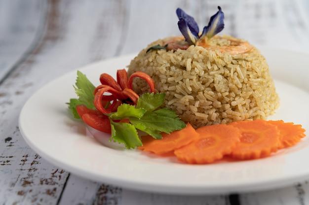 Ryż smażony z krewetkami na białym talerzu składającym się z pomidorów i marchwi.