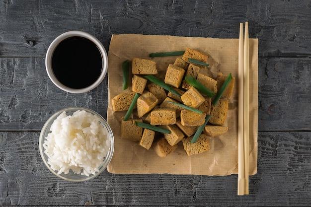 Ryż, sos sojowy, pałeczki i grillowany ser tofu na drewnianym stole. przystawka z grillowanego sera. leżał na płasko.